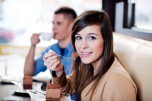 Mujer joven comiendo pastel de chocolate