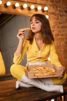 Mujer joven comiendo pizza sentado en un kombineh amarillo