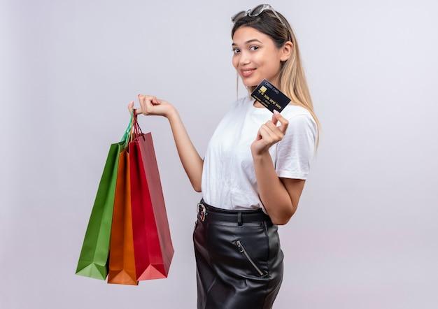 Una mujer joven complacida en camiseta blanca con gafas de sol en la cabeza mostrando la tarjeta de crédito mientras sostiene bolsas de la compra en una pared blanca