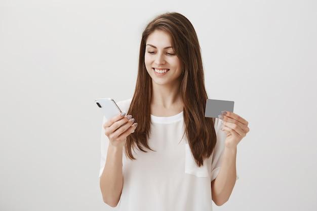 Mujer joven complacida de compras en línea, mostrando tarjeta de crédito y teléfono móvil