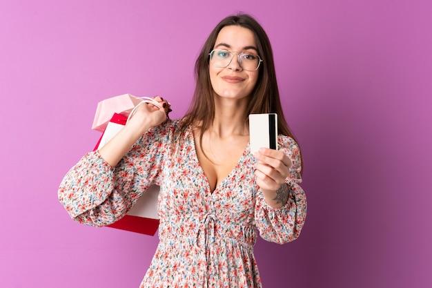 Mujer joven comprando algo de ropa sobre pared aislada