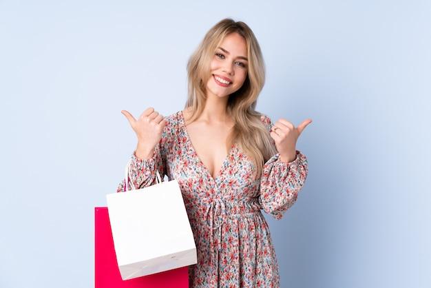 Mujer joven comprando algo sobre fondo azul aislado