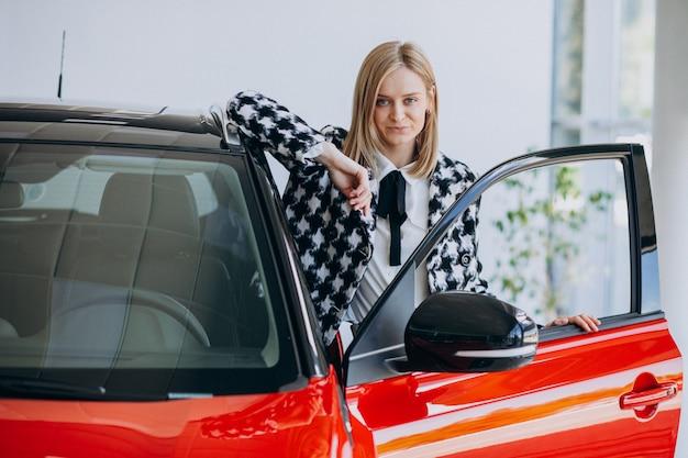 Mujer joven comprando un automóvil en una sala de exposición de automóviles