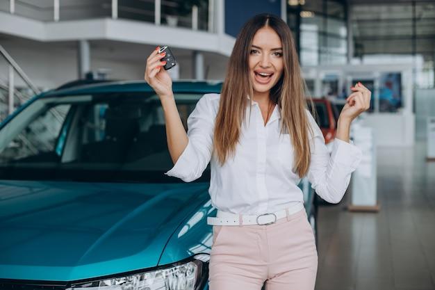 Mujer joven comprando un coche en una sala de exposición de coches