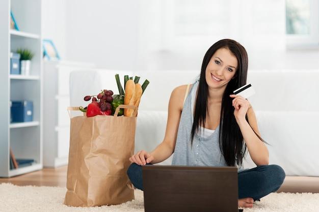 Mujer joven comprando comestibles en línea