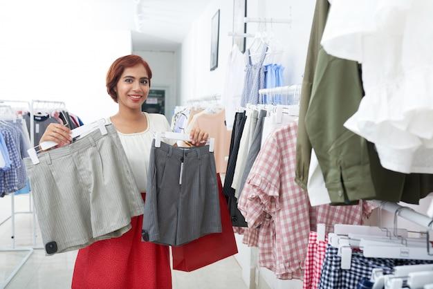 Mujer joven comprando pantalones cortos
