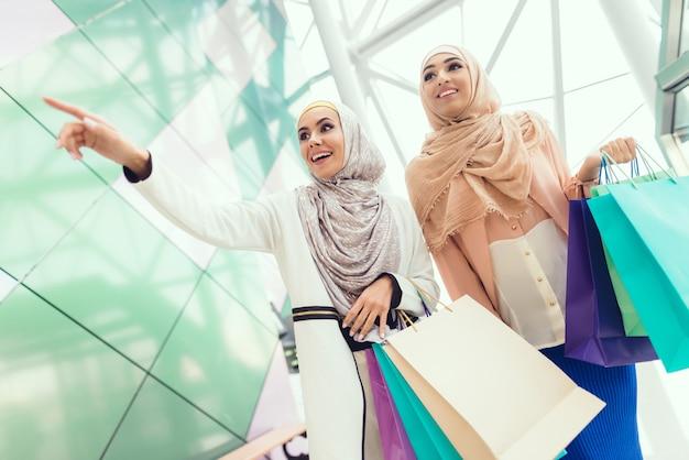 Mujer joven con compras en el centro comercial con un amigo.