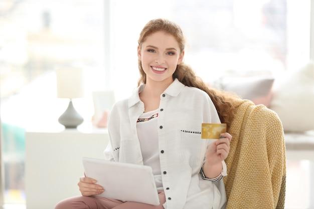 Mujer joven de compras en línea con tarjeta de crédito y tableta en casa