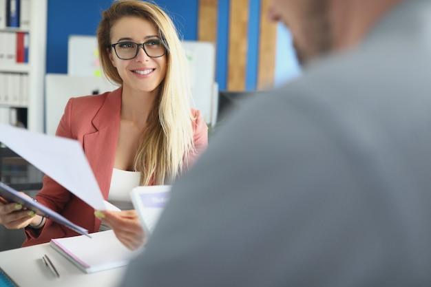 Mujer joven comprobación de documentos financieros de la empresa closeup
