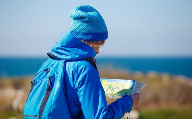 Mujer joven comprobación de mapa en la orilla del mar en viaje de senderismo. concepto de viaje