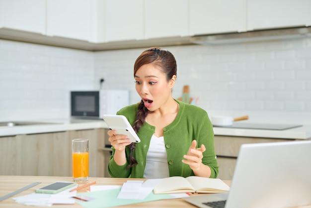 Mujer joven comprobando las facturas de su casa en la cocina
