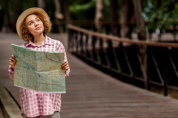 Mujer joven comprobando un mapa de un nuevo destino con espacio de copia
