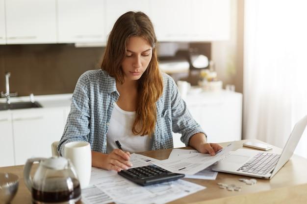 Mujer joven comprobando su presupuesto y haciendo impuestos