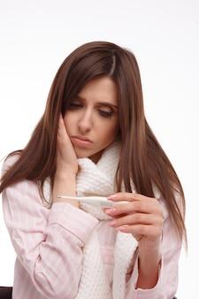 Mujer joven comprobando su temperatura con un termómetro