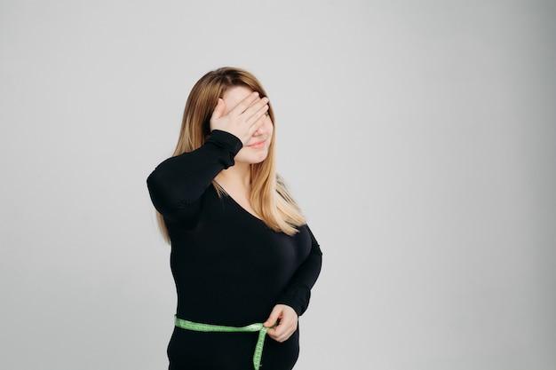 Mujer joven comprobar su grasa del estómago con cinta de línea, gesticular facepalm
