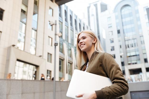 Mujer joven con computadora portátil caminando en la calle