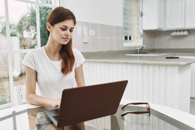 Mujer joven con una computadora portátil en la mesa trabajando y descansando