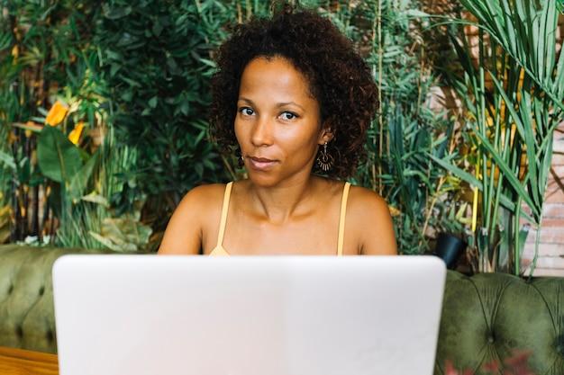 Mujer joven con la computadora portátil que mira la cámara