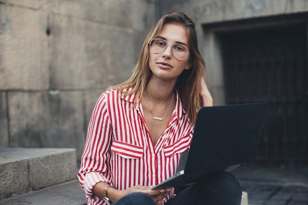 Una mujer joven con una computadora portátil sentada en las escaleras, cerca de la universidad