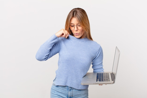 Mujer joven con una computadora portátil sintiéndose estresada, ansiosa, cansada y frustrada