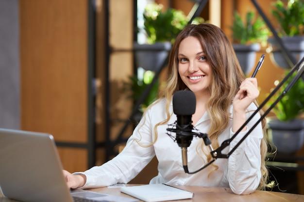 Mujer joven comunicándose con seguidores en línea en café