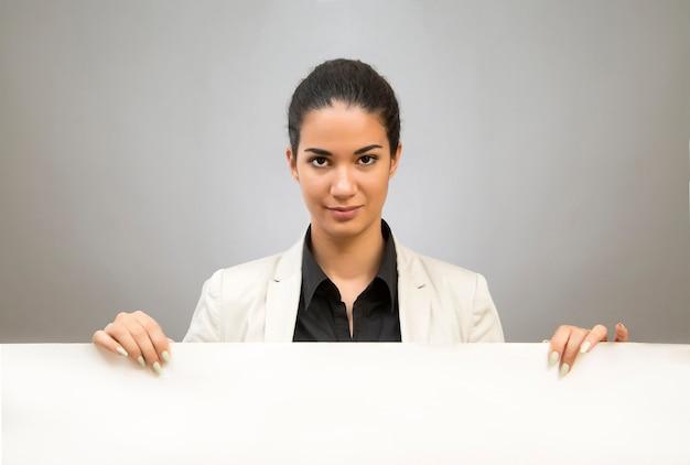 Mujer joven con el tablero en blanco