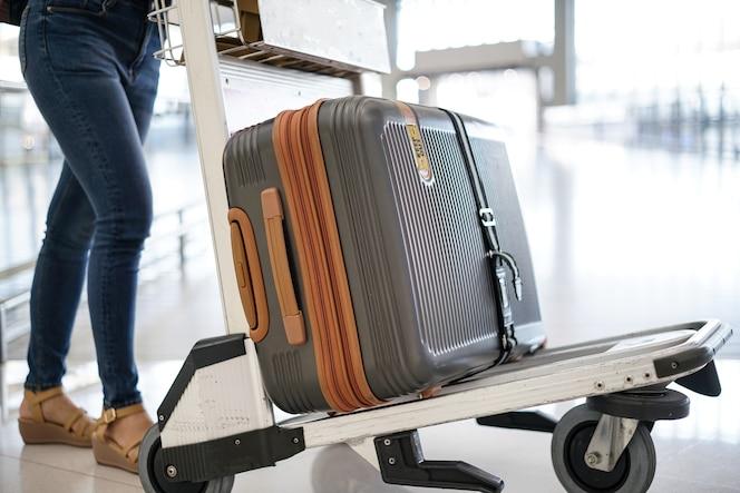Mujer joven con equipaje en el carro en el aeropuerto