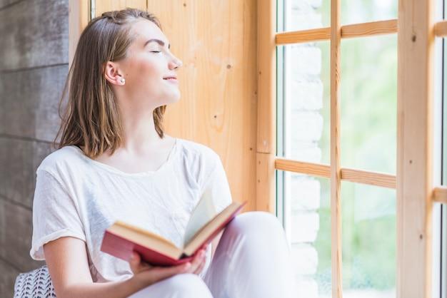 Mujer joven con ojo cerrado sosteniendo libro relajante cerca de la ventana