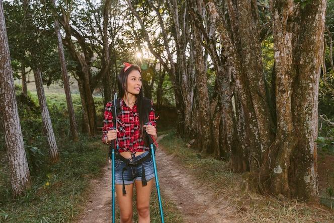 Mujer joven con senderismo polo explorar bosque