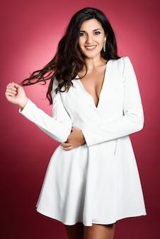 Mujer joven con un vestido blanco corto sonriendo a la cámara.