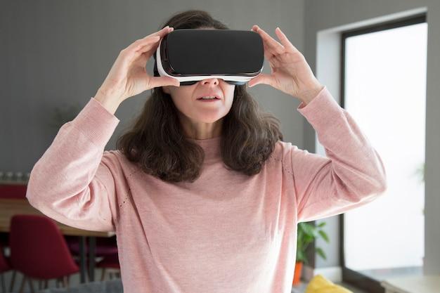 Mujer joven concentrada ajustando gafas de realidad virtual