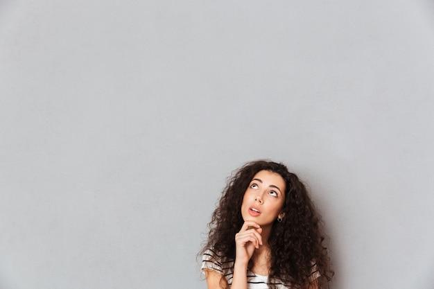 Mujer joven concentrada con cabello peludo tocando su barbilla con la cara hacia arriba y pensando o soñando sobre la pared gris