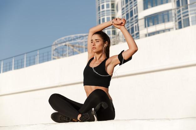 La mujer joven concentrada de los deportes hace ejercicios de estiramiento deportivos.