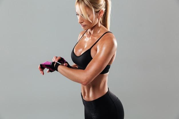 Mujer joven concentrada de los deportes que se coloca aislada mirando el reloj.