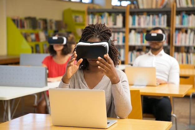 Mujer joven concentrada con gafas de realidad virtual