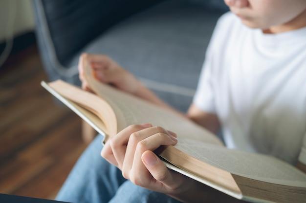 Mujer joven concentrada leyendo un libro con la mano de cerca.