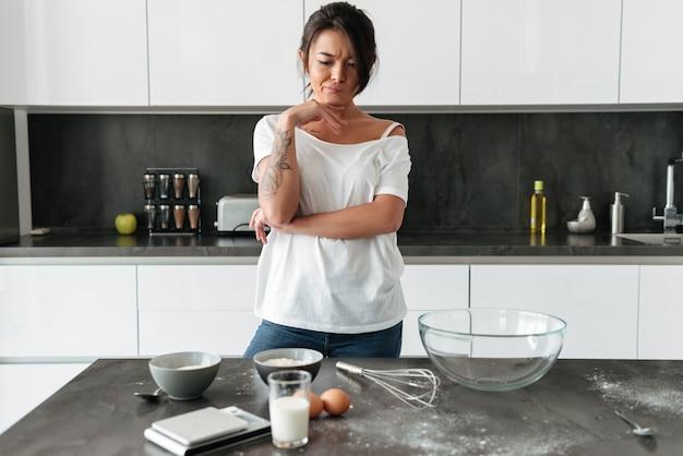 Mujer joven concentrada de pie en la cocina en casa