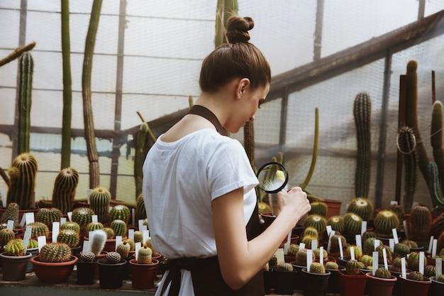 Mujer joven concentrada de pie en invernadero cerca de las plantas
