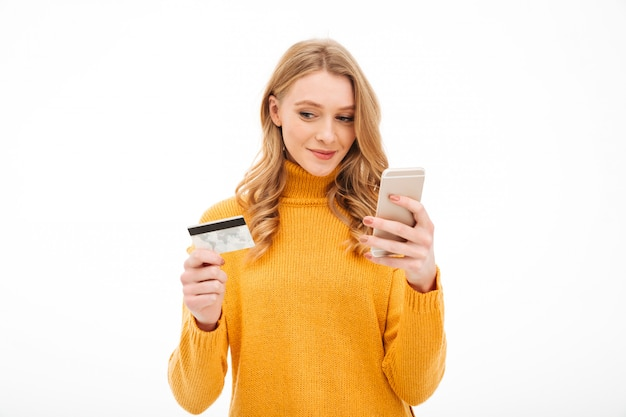 Mujer joven concentrada que sostiene el teléfono móvil y la tarjeta de crédito.