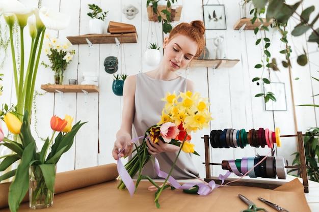 Mujer joven concentrada recogiendo coloridos bouquet en taller