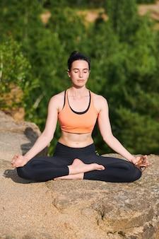 Mujer joven concentrada en ropa deportiva sentada con las piernas cruzadas y manteniendo los ojos cerrados mientras abre el chakra espiritual