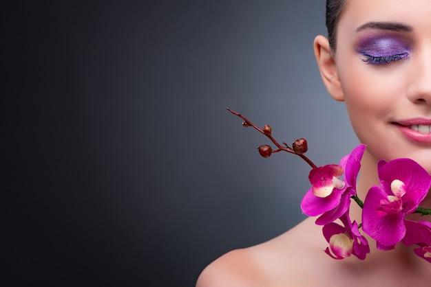 Mujer joven en concepto de belleza con flor de la orquídea