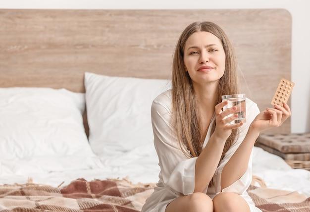 Mujer joven con condón y píldoras anticonceptivas en el dormitorio