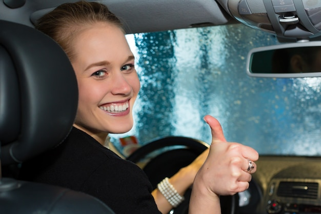 Mujer joven conduce coche en estación de lavado