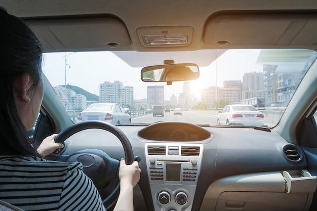 Mujer joven conduciendo el coche en taxi
