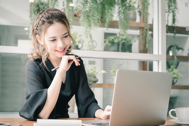 Mujer joven confiada de la felicidad que trabaja en la computadora portátil o el cuaderno en su oficina.