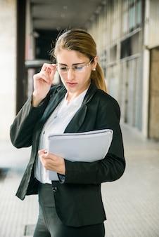 Mujer joven confiada que lleva a cabo el documento disponible