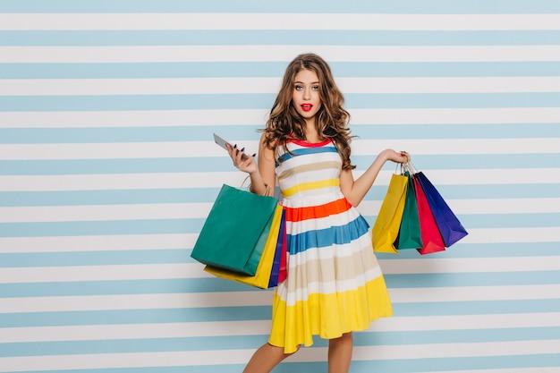 Mujer joven confiada que presenta con el teléfono y las compras. filmación en interiores de una curiosa niña de pelo largo con bolsas de boutique.