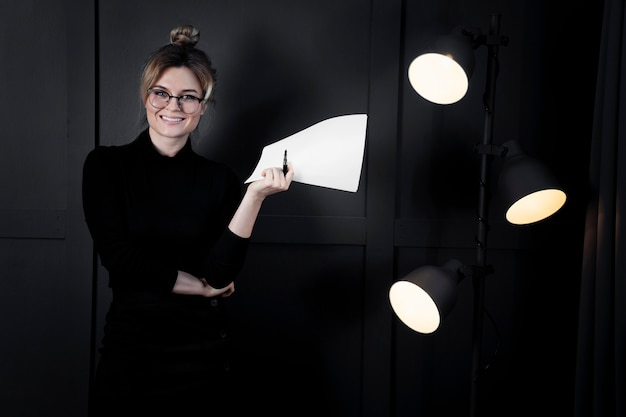 Mujer joven confiada que sostiene los papeles en la oficina