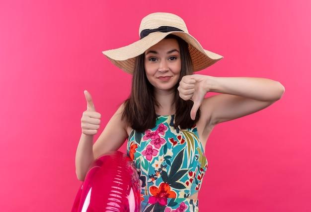 Mujer joven confiada con sombrero sosteniendo el anillo de natación y mostrando los pulgares hacia arriba y hacia abajo en la pared rosa aislada